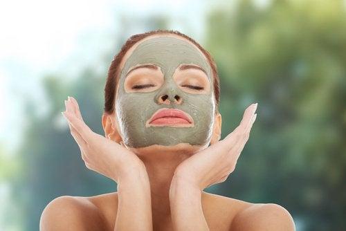 Eine Frau hat eine Gesichtsmaske aufgetragen und hält ihre Augen geschlossen.