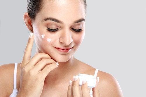 Frau trägt Creme im Gesicht auf