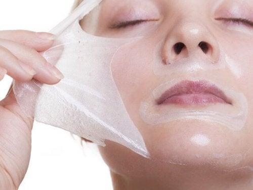 Eine Frau zieht sich ihre Gelatin- und Milchmaske vom Gesicht.