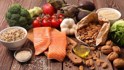 Viele gesunde Lebensmittel sind zu sehen, etwa Lachs, Olivenöl, Knoblauch und Tomaten.