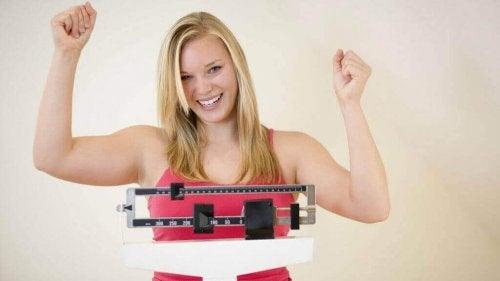 Eine Frau feiert ihren Gewichtsverlust.