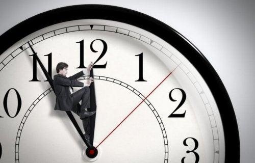 Ein Mann steht auf dem Zeiger einer Uhr.