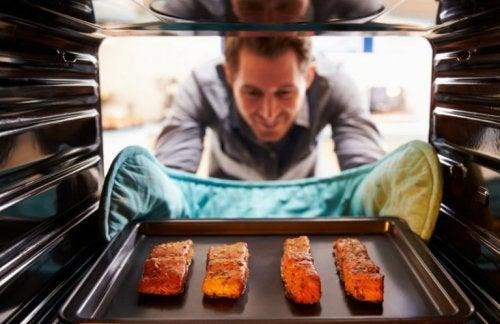 Mann holt Lachs aus dem Ofen