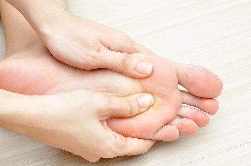 Jemand, der geschwollene Füße hat, massiert und reibt sie.