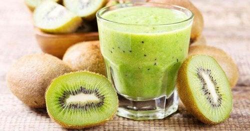 Eine Tasse mit Kiwi-Saft, um die herum viele Kiwis liegen.