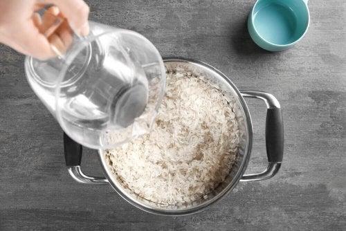 Etwas Wasser wird in einen Topf mit Reis gegossen.