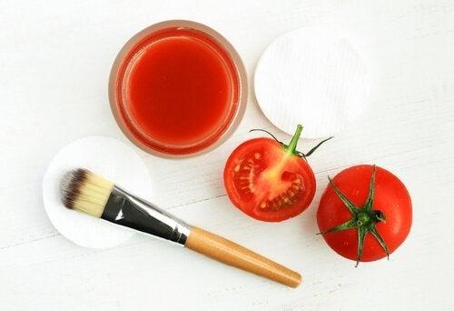 Eine Schale Tomatensaft, zwei Tomaten, ein Pinsel und Wattebäusche sind abgebildet.