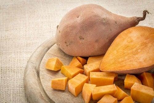 Zwei Süßkartoffeln, wobei eine aufgeschnitten ist.