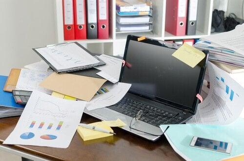 Ein ungeordneter Schreibtisch voller Dokumente und einem Laptop führt zu Prokrastination.