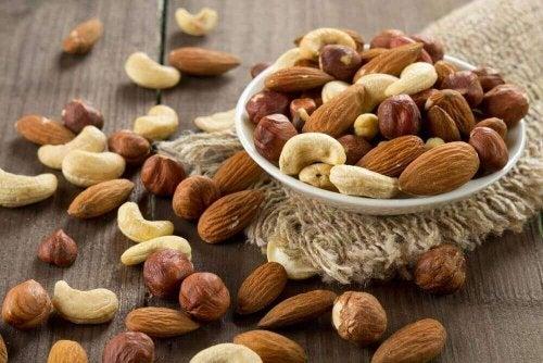 Eine kleine Schüssel ist gefüllt mit verschiedenen Nüssen, wie Cashew oder Mandeln.