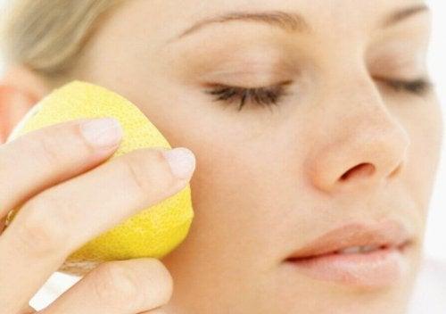 Eine Frau streicht sich eine Zitrone über die Wange.