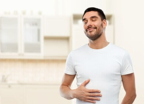 Vorteile von Zitronensaft sind auch Probleme mit der Verdauung zu beseitigen, weswegen der Mann im Foto zufrieden aussieht.