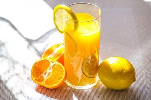 Ein Glas Zitronensaft, neben welchem Zitronen und Orangen liegen.