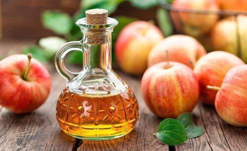 Apfelessig in einer Flasche, dahinter ein paar Äpfel.