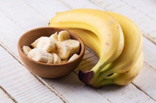 Eine Schale mit aufgeschnittenen Bananen, neben der ganze Bananen liegen.