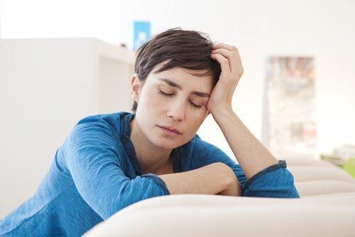 Frau mit chronischer Müdigkeit hält die Augen geschlossen.
