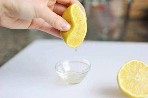 Eine Zitrone wird in eine kleine Schüssel ausgepresst.