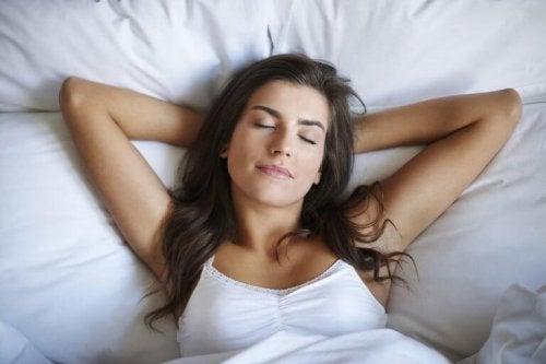 Eine Frau schläft zufrieden in ihrem Bett. Sie kennt unsere Tipps aus der Neurobiologie.
