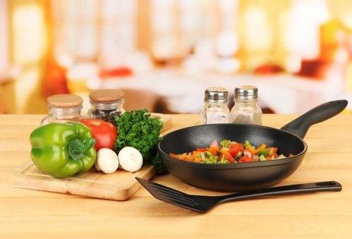 Eine Pfanne gefüllt mit Gemüse, daneben ein paar Gemüsesorten wie Paprika auf einem Schneidebrett.