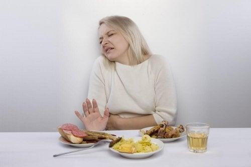 Eine Frau mit Bauchschmerzen möchte das Essen auf dem Tisch nicht essen.