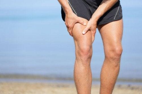Mann hat Krampf im Bein am Strand