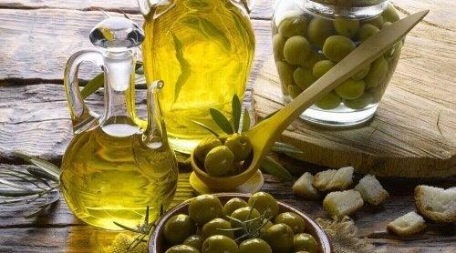Oliven in einer Schüssel und Olivenöl in zwei Flaschen.