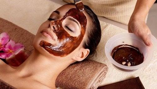 Eine Maske aus Schokolade und Mandelöl wird einer Frau aufgetragen.