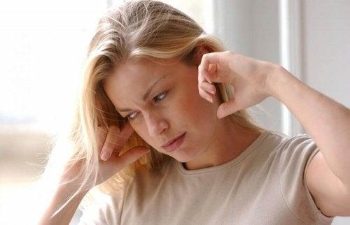 Frau hält sich die Ohren zu, weil sie Heilmittel gegen Ohrenschmerzen braucht.