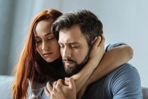 Eine Frau umarmt einen Mann und bietet ihm Unterstützung.