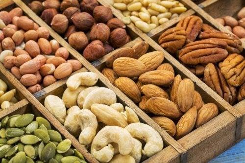 Verschiedene Nüsse in kleinen Boxen, wie Mandeln, Cashews oder Pinienkerne.