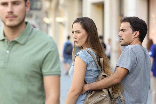 Warum sich Paare streiten: Eine Frau mit Freund starrt einem anderen Mann hinterher.