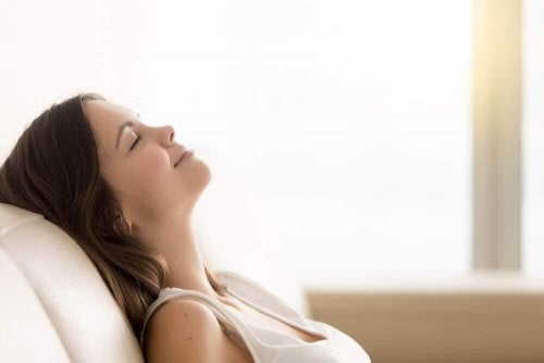 Eine Frau hat die Augen geschlossen und ruht sich auf der Couch aus.