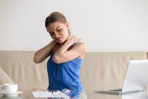 Eine Frau sitzt auf der Couch und hält sich ihren verspannten Nacken.