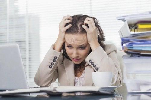 Eine gestresste Frau zieht an ihren Haaren.