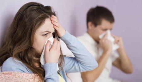 Mann und Frau schnäuzen sich, weil sie krank sind und Heilmittel aus Knoblauch brauchen.