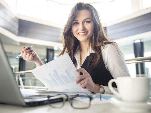 Eine lächelnde Frau sitzt an ihrem Schreibtisch.