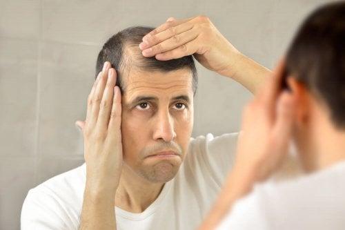 Mann schaut sich seine Geheimratsecken im Spiegel an