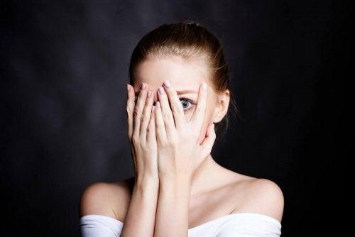 Eine Frau verdeckt sich das Gesicht mit ihren Händen.