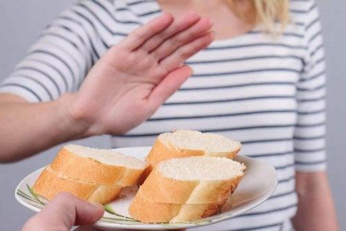 Eine Frau lehnt einen Teller mit weißem Brot ab.