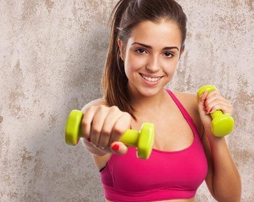 Frau hebt Gewichte, um ihre Brüste zu straffen