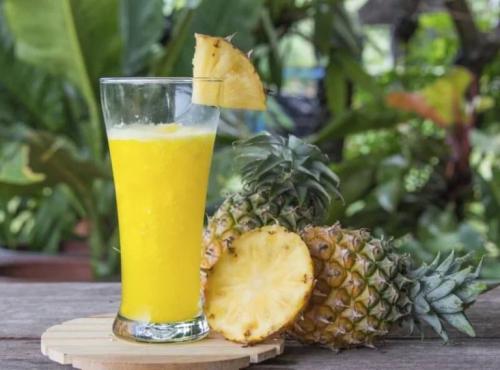 Ein Ananassaft und daben zwei ganze Ananas.