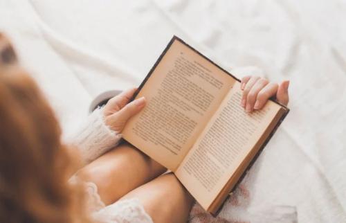 Eine Frau liest ein Buch, um ihre Sprachgewandtheit verbessern zu können.