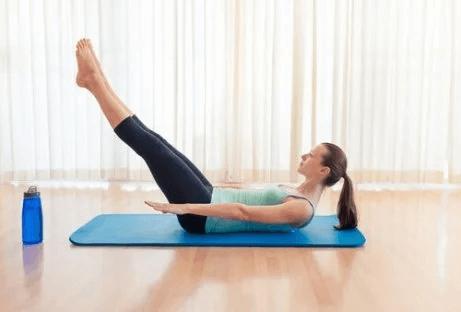 Eine Frau macht Übungen für einen knackigen Po, wie etwa die Beine anzuheben.