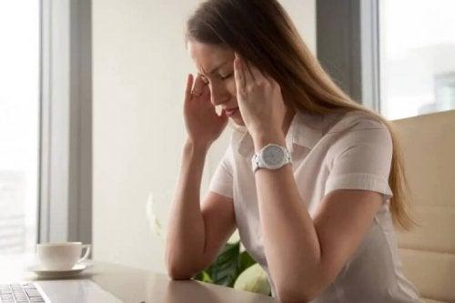 Eine gestresste Frau, die sich den Kopf hält.