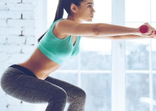 Eine Frau macht Kniebeugen, da sie Übungen für einen knackigen Po ausführt.