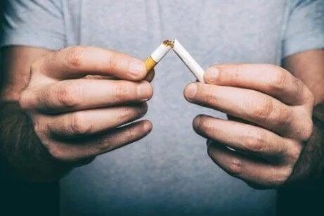 Ein Mann bricht eine Zigarette auseinander, um mit dem Rauchen aufzuhören.