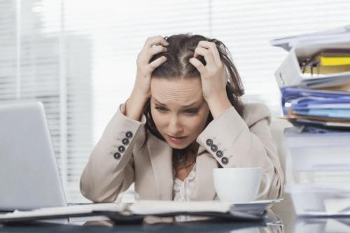Eine verzweifelte Frau sitzt in der Arbeit vor ihrem Schreibtisch.