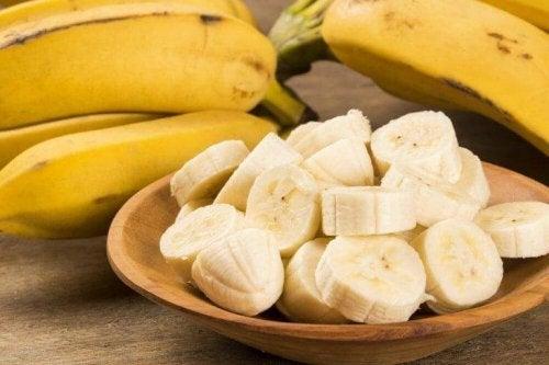 Eine Schale mit aufgeschnittener Banane und dahinter einige ganze Bananen.