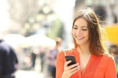 Eine Frau schaut aufs Handy und geht am Gehsteig.
