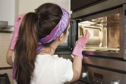 Frau reinigt Mikrowelle